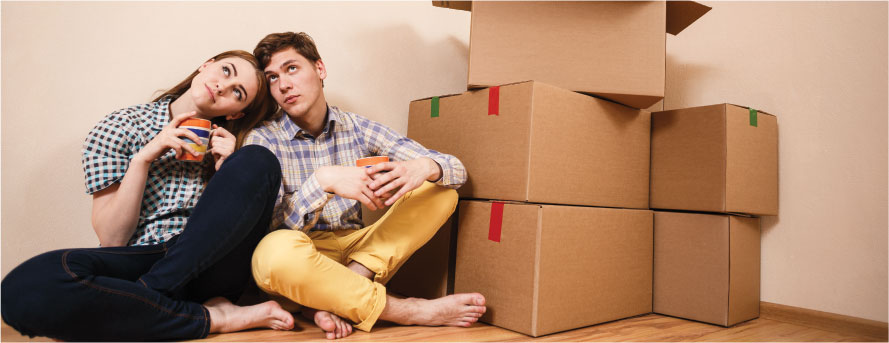 photo of a couple finished packing sitting next to the boxes on the floor