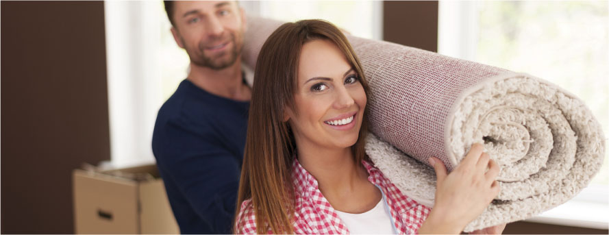 photo of a smiling couple carrying a carpet