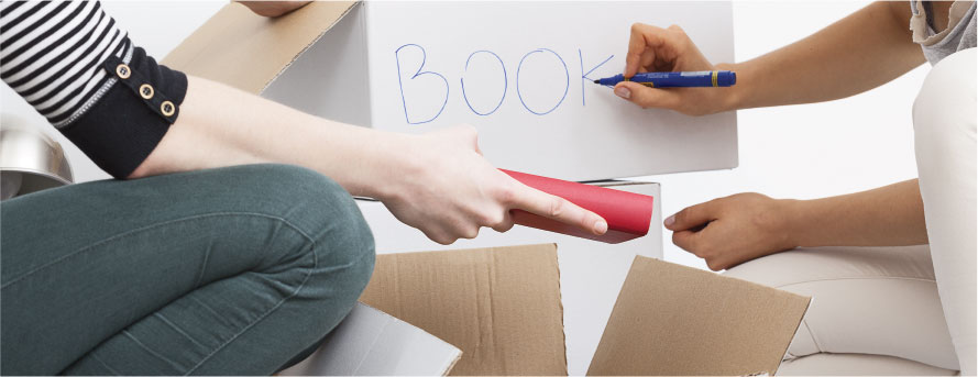 photo of two women packing home items and marking the boxes